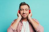 pozitivní muž poslech hudby se sluchátky, izolované na modré