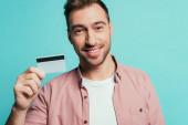šťastný vousatý muž držící kreditní kartu, izolovaný na modré