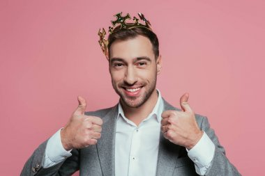 Handsome smiling man in crown and suit showing thumbs up, isolated on pink stock vector