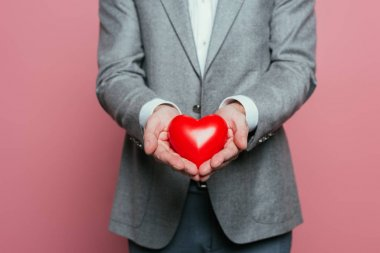 Cropped view of man holding red heart for valentines day, isolated on pink stock vector