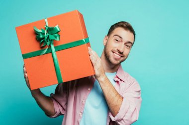 Smiling man holding big gift box, isolated on blue stock vector