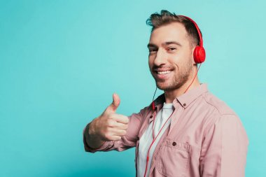 cheerful man listening music with headphones and showing thumb up, isolated on blue