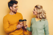 happy man and woman looking at each other while clinking with paper cups on yellow background