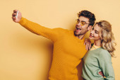 cheerful man taking selfie on smartphone with pretty girlfriend on yellow background