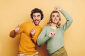 šťastný pár tanec při poslechu hudby v bezdrátových sluchátkách na žlutém pozadí