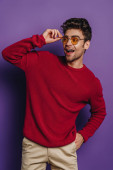 veselý muž dotýká brýle, zatímco stojí s rukou v kapse a odvrací pohled na fialové pozadí