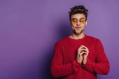 mazaný muž gestikuluje spojenými prsty na purpurovém pozadí