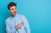 vzrušený mladý muž dívá pryč a směje se, zatímco ukazuje prstem na modré pozadí
