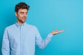 usmívající se mladý muž dívá na otevřené rameno na modrém pozadí