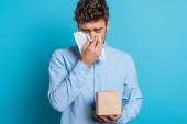 kranker junger Mann niest in Papierserviette auf blauem Hintergrund