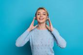 fröhliches Mädchen lächelt in die Kamera, während es Musik in drahtlosen Kopfhörern auf blauem Hintergrund hört