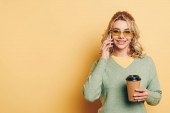 cheerful girl talking on smartphone, holding coffee to go and smiling at camera on yellow background