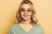 gyönyörű, boldog lány szemüvegben mosolyog a kamera sárga háttér