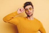 pohledný, sebevědomý muž dotýká brýle při pohledu na fotoaparát na žlutém pozadí