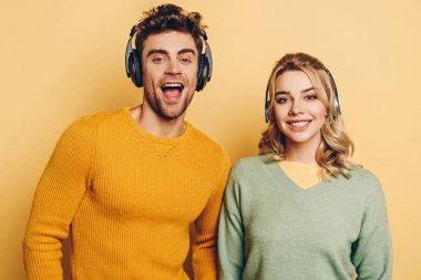 happy man and woman smiling at camera while listening music in wireless headphones on yellow background
