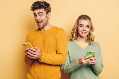 Cheerful man and woman smiling at camera while messaging on smartphones on yellow background stock vector