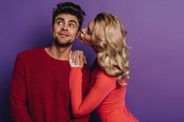 Pretty girl kissing happy boyfriend looking away on purple background stock vector