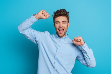 Excited young man showing winner gesture while smiling at camera on blue background stock vector