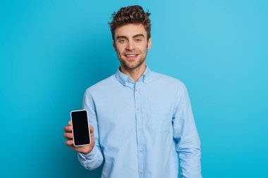 Handsome young man smiling at camera while showing smartphone with blank screen on blue background stock vector