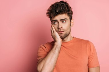 upset young man touching chick while suffering from toothache on pink background