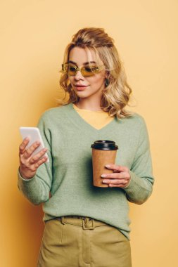 Stylish, smiling girl holding coffee to go while chatting on smartphone on yellow background stock vector