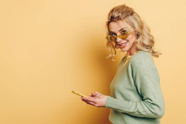 Pretty girl in glasses chatting on smartphone and smiling at camera on yellow background stock vector