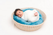 cute newborn mixed race baby wrapped in blanket lying in basket on white