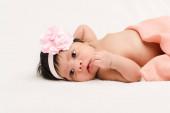 Fotografie adorable bi-racial newborn baby in headband lying on white