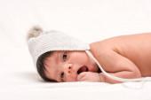 rozkošné bi-rasové novorozeně v pleteném klobouku ležícím na bílém