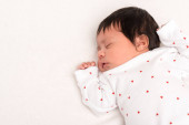 vrchol pohled na rozkošný bi-rasové novorozence v batole spací izolované na bílém
