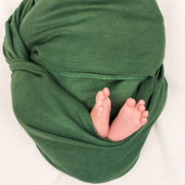 oříznutý pohled na dítě zabalené v zelené přikrývce ležící na bílém