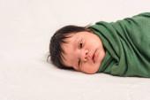 roztomilý bi-rasové dítě zabalené v zelené dece ležící na bílém