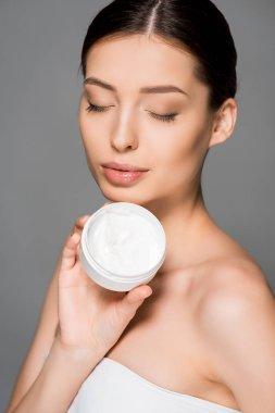 Beautiful girl with closed eyes holding moisturizing cream, isolated on grey stock vector