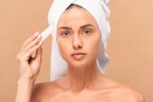 nahý dívka v ručníku držení ošetření krém v blízkosti obličeje s problémem kůže izolované na béžové