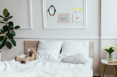 interior of empty children room with bed, teddy bear and paintings