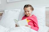 rozkošné usměvavé dítě čtení knihy, zatímco sedí na posteli