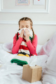 Fotografie krankes Kind mit laufender Nase hält Servietten im Bett