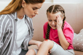 matka drží nohu s zraněním na koleni, zatímco emocionální dcera pláče doma