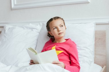 Pensive kid reading book while sitting on bed stock vector