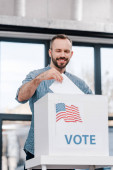 Photo happy bearded man voting and putting ballot in box with vote lettering