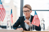 selective focus of beautiful diplomat in eyeglasses touching microphone near american flags