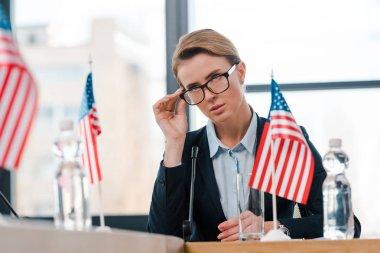 Selective focus of beautiful diplomat touching eyeglasses near american flags stock vector