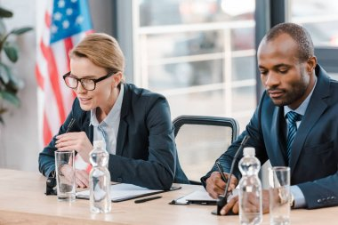 Attractive diplomat talking in microphone near african american representative stock vector