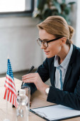 selective focus of attractive diplomat in eyeglasses touching microphone near clipboard and american flag