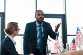 selektivní zaměření atraktivní diplomat při pohledu na africký Američan gestikuluje při rozhovoru v blízkosti vlajek Ameriky