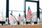 Photo selective focus of american flags near glasses and bottles with water on table