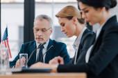 selective focus of bearded businessman near attractive diplomats