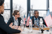 selective focus of attractive businesswoman looking at african american diplomat
