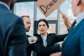 Photo selective focus of businessman standing near attractive journalist with microphone reaching multicultural diplomats while holding placard