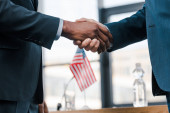 Photo cropped view of multicultural diplomats shaking hands near flag of america